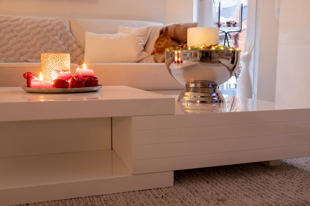 A cozy low light living room couch with candles and silver bowl.